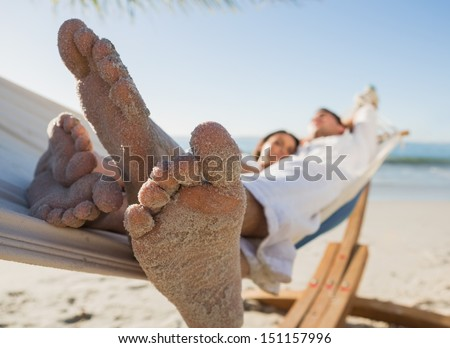 Close up of sandy feet of couple in a hammock on the beach - stock photo