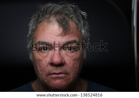 Close up of scary-looking man with gray hair & an unshaven appearance - stock photo