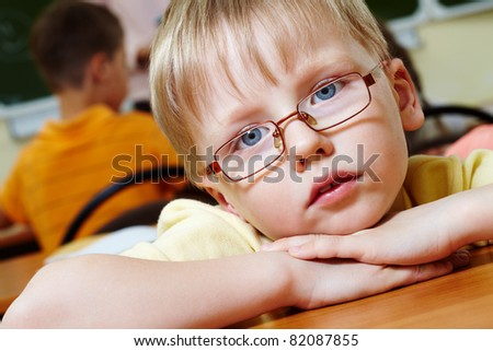 Close-up of schoolboy putting his head on arms and looking at camera - stock photo
