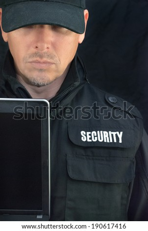 Close-up of security holding a laptop display to camera. - stock photo