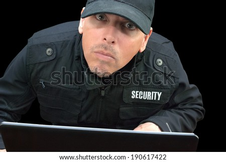 Close-up of security working on a laptop, looking to camera.