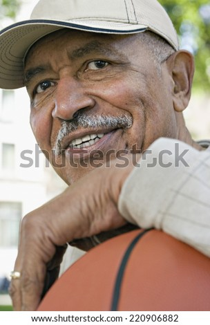 Close up of senior African man smiling with basketball - stock photo
