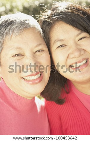Close up of senior Asian mother and grown daughter smiling