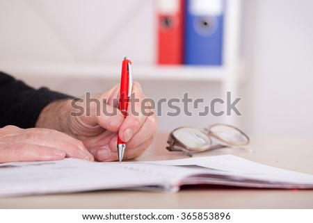 Close up of senior businessman's hand writing notes with red pencil on the desk in the office - stock photo