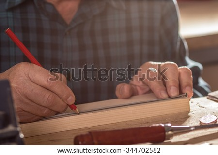 Close up of senior carpenter hands marking a measurement on a wooden plank - stock photo