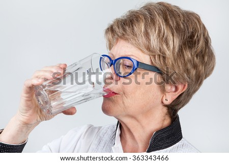 Close up of senior Caucasian woman drinking water from glass, gray background - stock photo