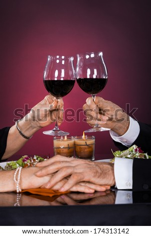 Close-up Of Senior Couple Hand Toasting Wineglass At Dinner - stock photo