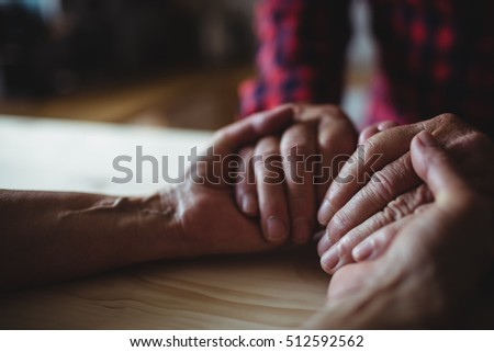 Close-up of senior couple holding hands at home