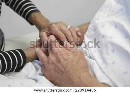 Close up of senior couple holding hands in hospital - stock photo