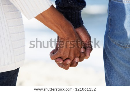 Close Up Of Senior Couple Holding Hands On Beach - stock photo