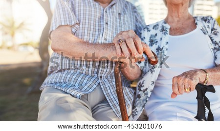Close up of senior couple holding hands while sitting on the park bench together. Retired man and woman with walking cane. Focus on hands. - stock photo