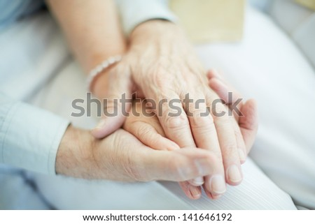 Close-up of senior male holding the hand of his wife - stock photo