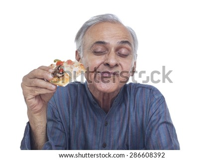 Close-up of senior man eating pizza with eyes closed