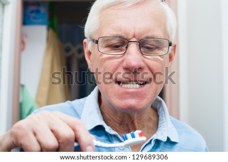 Close up of senior man going to brush his teeth. - stock photo