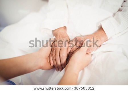 Close-up of senior woman and nurse holding hands - stock photo