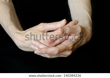 Close up of senior woman's hands in different positions on black background. Here one hand protects the other