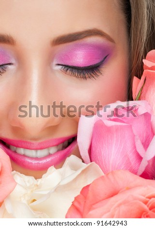 Close-up of sensual beautiful woman with roses and stylish bright make-up. Woman with closed eyes