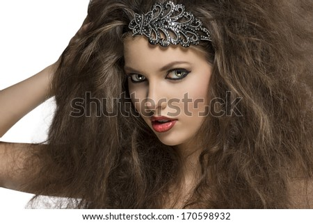 close-up of sensual brunette woman with voluminous curly hair-style, glitter accessory in the hair and strong make-up  - stock photo
