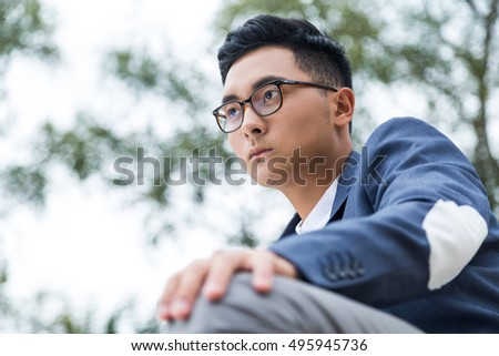 Close up of serious Asian man in blue suit wearing glasses and sitting in the street thinking about his place in life. Concept of pondering and life choices.