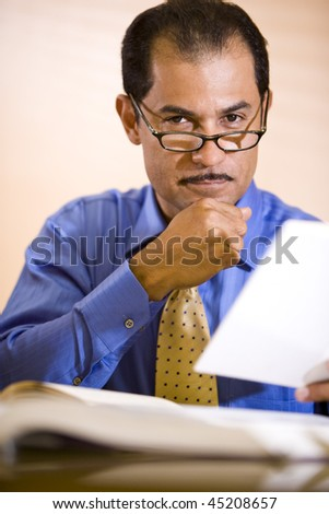Close-up of serious middle-aged Hispanic businessman working in office reading reference books - stock photo