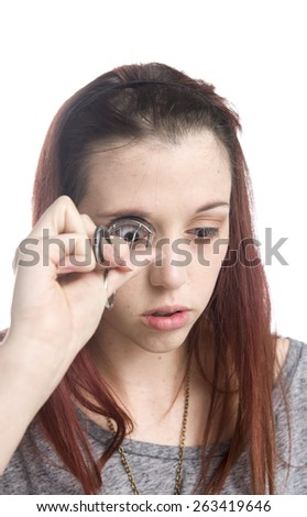 Close Up of Serious Young Teenage Girl Curling Eyelashes with Eyelash Curler with White Background - stock photo