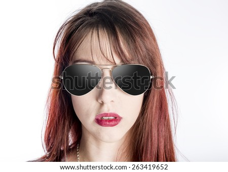 Close Up of Serious Young Woman with Attitude Wearing Aviator Style Sunglasses with Dark Lenses on White Background - stock photo