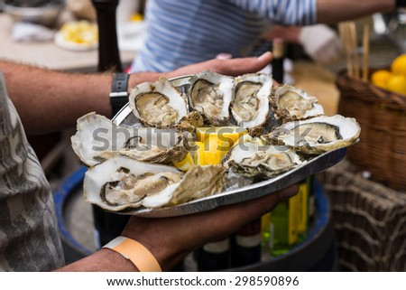 Close Up of Server with Tray of Fresh Shucked Oysters with Lemon Served as Appetizer - stock photo