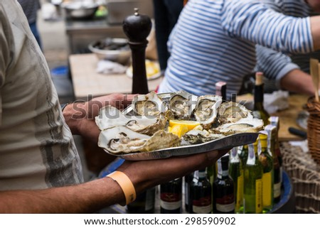 Close Up of Server with Tray of Fresh Shucked Oysters with Lemon Wedges Served as Appetizer - stock photo