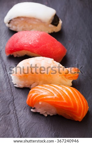 Close-up of set of four sushi with salmon, tuna, scallop and shrimp on a black background - stock photo