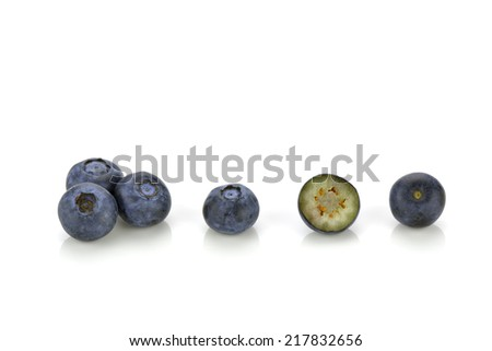 Close-up of several blueberries, one is cut in half - stock photo