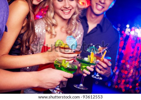 Close-up of several cocktails in hands of young people during party