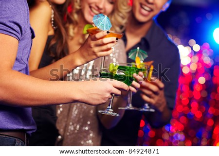 Close-up of several cocktails in hands of young people having party
