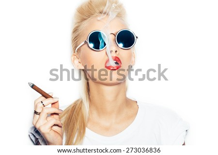 Close-up of sexy woman in sunglasses and white t-shirt blowing smoke from a cigar.  White background, not isolated - stock photo