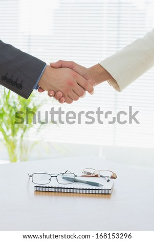 Close-up of shaking hands over eye glasses and diary after a business meeting at office desk - stock photo