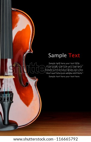 Close up of shiny violin on wooden table, isolated on black background, with clipping path - stock photo