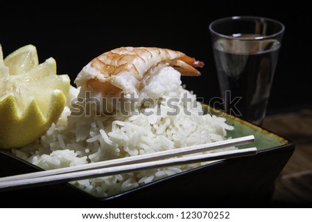 Close up of shrimp sushi on a bowl of white rice with lemon and chopsticks with a glass of sake - stock photo