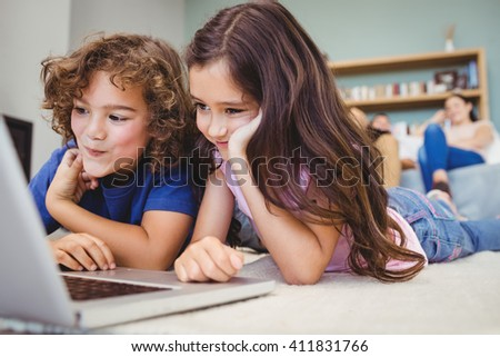 Close-up of siblings looking in laptop on carpet at home