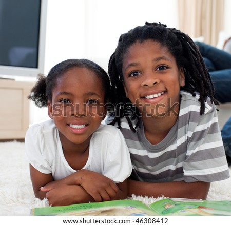Close-up of siblings reading lying on the floor - stock photo