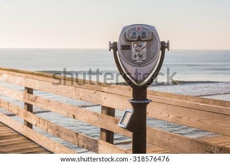 Close-Up of Sightseeing Binoculars with Beach Background on the Virginia Beach Fishing Pier - stock photo