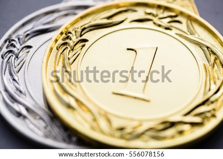 Close-up of silver and golden medal with embossed number one and decorative laurels