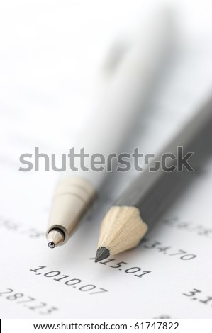 Close-up of silver pen and black pencil on paper table numbers. - stock photo