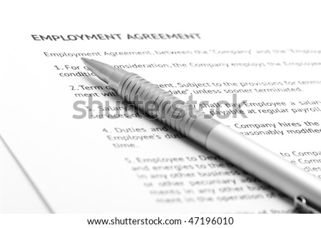 Close-up of silver pen on employment agreement. Selective focus on top of pen. - stock photo