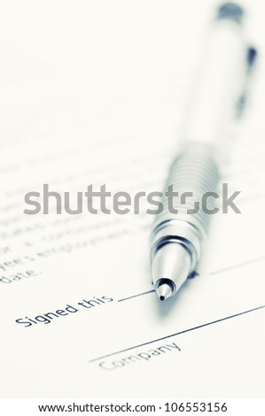 Close-up of silver pen on employment agreement. Selective focus on top of pen. Toned image. - stock photo
