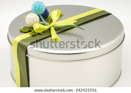 Close up of silver rounded box full of fresh baked cookies or bakery for giving as present for holiday season on white background