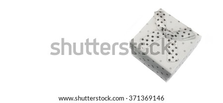 Close Up Of Single Gift Box With Dotted Black White Pattern And White Ribbon And Bow, Isolated On White Background,  Horizontal Image, Copy Space, Overhead  View - stock photo