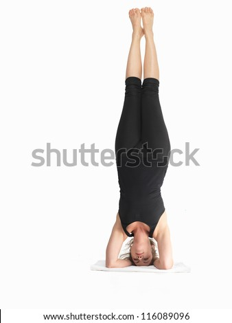 close up of single young woman in advanced yoga posture, dressed in blak, on white background - stock photo