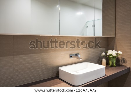 Close up of sink and mirror in modern bathroom - stock photo