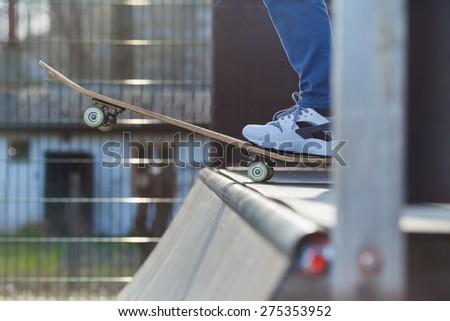 Close-up of skater's leg on a skateboard at the edge of a skate ramp preparing for a jump - stock photo