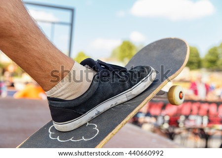 Close-up of skater's leg on a skateboard while preparing for a jump on a skate ramp - stock photo