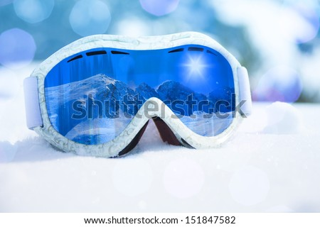 Close-up of ski and snowboard mask with mountain reflection in it - stock photo